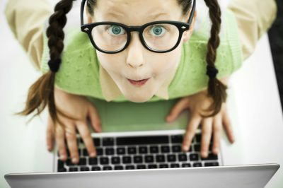 Above view of a girl geek . She is using her laptop and looking at the camera.  [url=http://www.istockphoto.com/search/lightbox/9786682][img]http://dl.dropbox.com/u/40117171/children5.jpg[/img][/url]