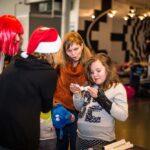 Mikołajki 2017, grupa osób, loteria losowa, dziewczynka czytająca karteczkę