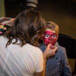 Mikołajki 2017 - kobieta maluje na twarzy chłopca maskę Spidermana