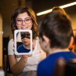 Mikołajki 2017 - malowanie twarzy, uśmiechnięta kobieta pokazuje w lusterku twarz pomalowanego chłopca