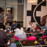 Mikołajki 2017 - sala, grupa ludzi przy niskich stołach do warsztatów plastycznych