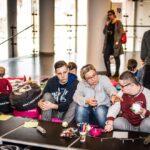 Mikołajki 2017 - warsztaty plastyczne, kobieta i dwóch chłopców przy stole