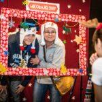 Mikołajki 2017, kobieta i chłopiec, pozują do zdjęcia za świąteczną ramą