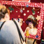 Mikołajki 2017, świątecznie ozdobiona rama, za nią pozuje przebrana dziewczynka