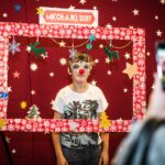 Mikołajki 2017 - chłopiec pozujący do zdjęcia za świąteczną ramą