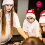 Mikołajki 2017- wolontariusze w białych koszulkach z logo fundacji i świątecznych czapkach