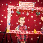 Mikołajki 2017, chłopiec pozujący do zdjęcia, przed nim świąteczna rama