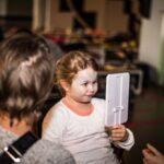Mikołajki 2017, malowanie twarzy, dziewczynka przegląda się w lusterku