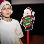 """Mikołajki 2017, chłopiec, tabliczka z napisem """"Santa stop here"""""""