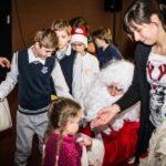 Mikołajki 2017, grupa osób, rozdawanie prezentów, w środku siedzący Mikołaj