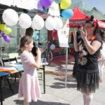 kobieta przebrana za Myszkę Miki uczy dziewczynkę języka migowego