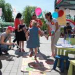 piknik miejski, dziewczynka gra w klasy, wokół obserwujący ludzie
