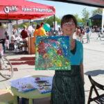 piknik miejski, kobieta pokazuje swój obraz, uśmiecha się