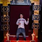 """młody chłopak pozuje do zdjęcia, przed nim złota rama z napisem """"Cinema Festival"""""""