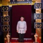 """dziewczyna z zespołęm downa pozuje do zdjęcia, przed nią złota rama z napisem """"Cinema Festival"""""""
