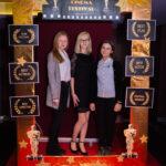 """trzy młode dziewczyny pozują do zdjęcia, przed nimi złota rama z napisem """"Cinema Festival"""""""