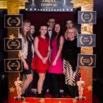 """grupa osób pozuje do zdjęcia, przed nimi złota rama z napisem """"Cinema Festival"""""""