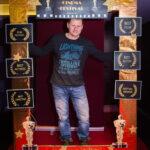 """mężczyzna pozuje do zdjęcia, przed nim złota rama z napisem """"Cinema Festival"""""""