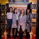 """grupa młodych osób pozuje do zdjęcia, przed nimi złota rama z napisem """"Cinema Festival"""""""