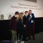 grupa młodych cieszących się z odebranej nagrody, młody chłopak mówi do mikrofonu trzymanego przez prowadzącego galę