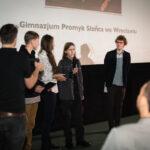 grupa młodych osób cieszących się z odebranej nagrody, młody chłopak mówi do mikrofonu patrząc w stronę publiczności