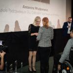 młoda dziewczyna przyjmuje gratulacje od kobiety - dyrektora fundacji, obok niej mężczyzna na wózku