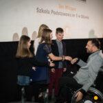 grupa młodych osób przyjmuje gratulacje od mężczyzny na wózku