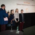 grupa młodych osób odbiera nagrodę, prowadzący mówi, patrząc na nich, do mikrofonu
