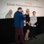 grupa młodych osób przyjmuje nagrodę, jedna z dziewczyn mówi do mikrofonu