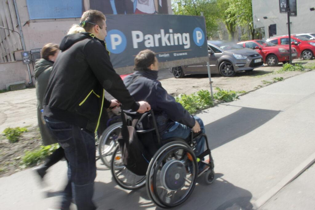 mężczyzna na wózku inwalidzkim na chodniku, wózek prowadzi asystent