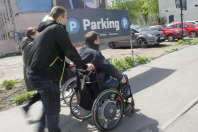mężczyzna na wózku inwalidzkim na chodniku