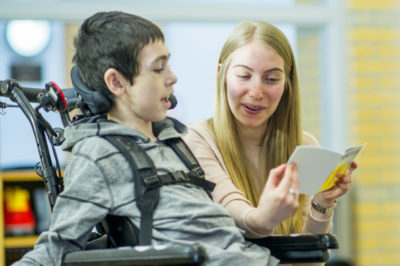 A caregiver is playing with a boy with a physical disability - he is sitting in a wheelchair and smiling happily.