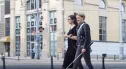 niewidoma kobieta z laską idzie ulicą, prowadzi ją asystentka