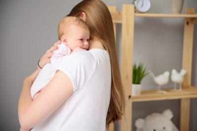 So tender embrace. Mother hugging her little cute child and holding her in arms, standing in bedroom